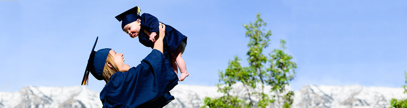 young woman and baby in graduation caps and gowns